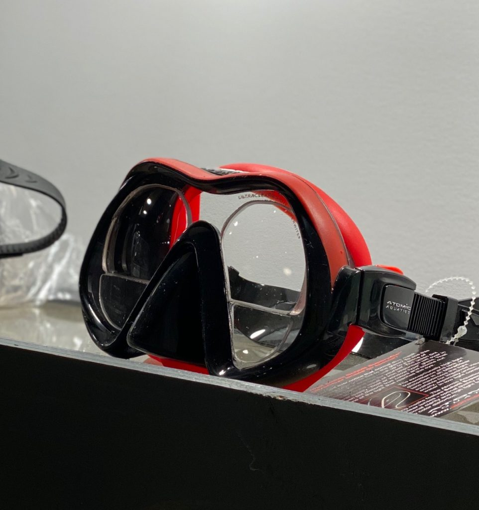 A dive mask sitting on a shelf containing lined bifocals.