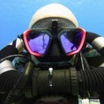 A diver under blue water in Cozumel, Mexico is wearing a scuba pro d mask as well as a Hollis Rebreather.