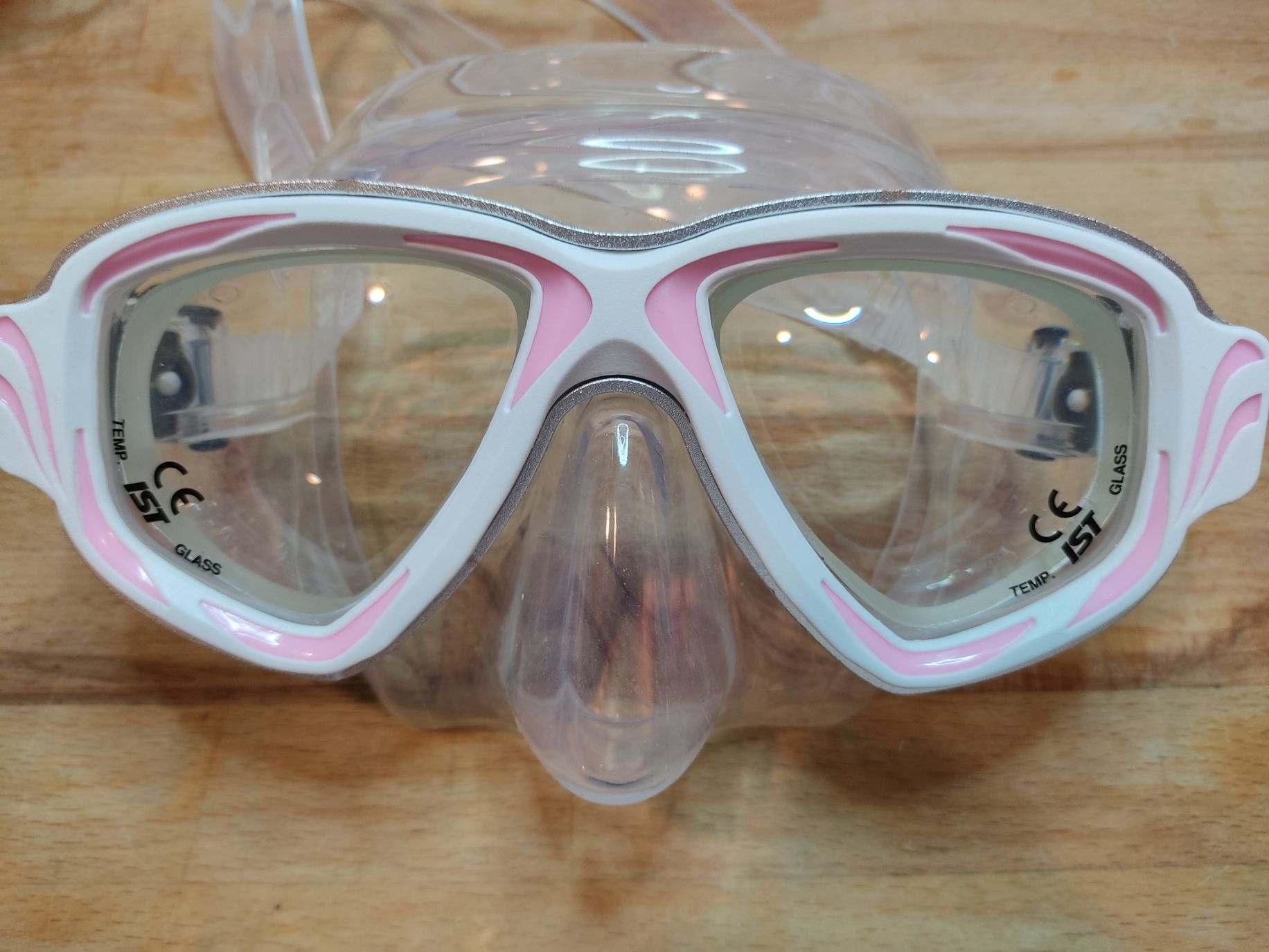 Scuba diving mask with light pink frame and higher strength prescription lenses.
